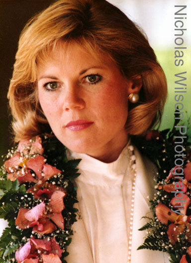 Candid portrait of a pensive bride wearing a lei of flowers